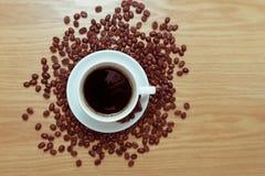 Tazza bianca con caffè nero e caldo che sta sui semi di cacao torrefatti marroni e sulla tavola di legno Immagini Stock Libere da Diritti