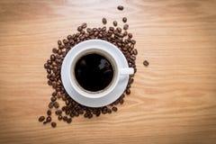 Tazza bianca con caffè nero e caldo che sta sui semi di cacao torrefatti marroni e sulla tavola di legno Fotografia Stock