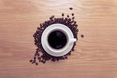 Tazza bianca con caffè nero e caldo che sta sui semi di cacao torrefatti marroni e sulla tavola di legno Fotografie Stock