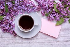 Tazza bianca con caffè o tè, nota, un mazzo dei lillà su un fondo di legno fotografia stock libera da diritti