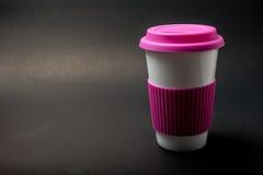 Tazza bianca con gli accessori rosa su fondo nero Immagine Stock