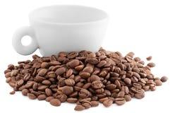 Tazza bianca con i chicchi di caffè immagine stock