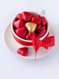 Tazza bianca con i cuori del cioccolato Immagine Stock