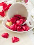 Tazza bianca con i cuori del cioccolato Fotografia Stock