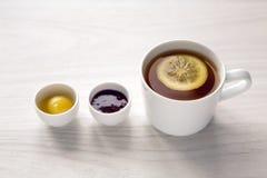 Tazza bianca con tè ed il limone, miele dell'inceppamento Immagine Stock