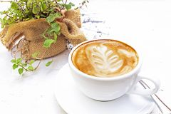 Tazza bianca di caffè caldo su di legno con il vaso della pianta e della tavola a fondo immagine stock