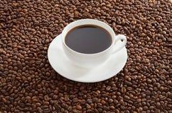 Tazza bianca di caffè nero che sta sui chicchi di caffè arrostiti Immagine Stock Libera da Diritti