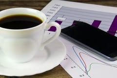 Tazza bianca di caffè nero, dei grafici, del telefono e dei dollari fotografia stock