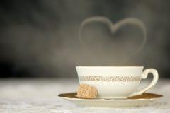 Tazza bianca di tè caldo con un fumo del cuore Immagini Stock
