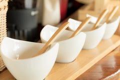 Tazza bianca e cucchiaio di legno sulla tavola Fotografia Stock