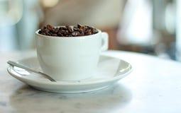Tazza bianca riempita di chicchi di caffè arrostiti Immagine Stock Libera da Diritti