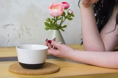 Tazza bianca su un supporto di legno, mano femminile fotografia stock libera da diritti