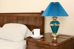 Tazza bianca su un tavolino da notte Fotografie Stock Libere da Diritti