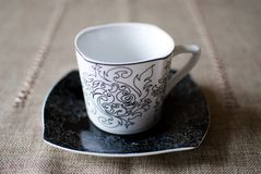 Tazza bianca sul piattino nero Fotografia Stock