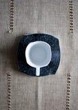 Tazza bianca sul piattino nero Immagini Stock