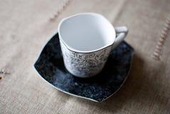 Tazza bianca sul piattino nero Fotografie Stock Libere da Diritti