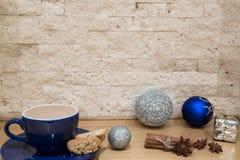 Tazza blu con cioccolata calda, i biscotti ed i decori d'argento di Natale fotografia stock