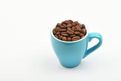 Tazza blu del caffè espresso in pieno dei chicchi di caffè sopra bianco Fotografia Stock