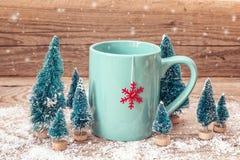 Tazza blu del tè di Natale con il fiocco di neve rosso e gli abeti miniatura sopra Immagini Stock