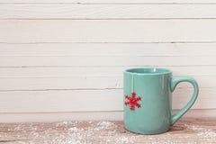 Tazza blu del tè di Natale con il fiocco di neve rosso sulla tavola di legno Immagine Stock Libera da Diritti