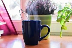 Tazza blu di tè pieno di vapore caldo dalla finestra fotografie stock