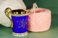 Tazza blu e palle rosa e bianche di filato Immagini Stock Libere da Diritti