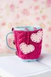 Tazza blu in maglione rosa con i cuori del feltro che stanno su un taccuino Fotografie Stock Libere da Diritti
