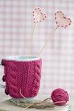 Tazza blu in un maglione rosa con i cuori del feltro Fotografie Stock