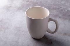 Tazza ceramica bianca dello spazio in bianco vuoto sul bordo del cemento fotografia stock