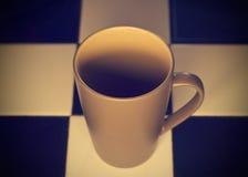 Tazza ceramica dell'oro di tono astratto di colore sul fondo delle mattonelle immagine stock