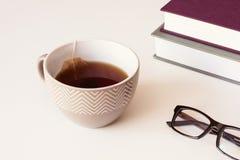 Tazza ceramica di Brown con le bustine di tè della carta e del tè, i vetri di lettura ed i libri sulla tavola Immagine Stock Libera da Diritti