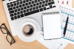 Tazza, computer portatile e blocco note di caffè sopra le carte con i numeri ed il carbone Fotografia Stock