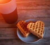 Tazza con caffè e due cuori sulla tavola di legno fotografia stock libera da diritti