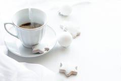 Tazza con caffè, i biscotti e le palle di Natale, alta chiave Fotografia Stock