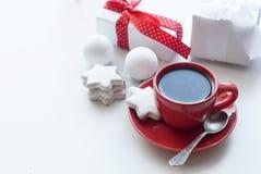 Tazza con caffè, il contenitore di regalo bianco, i biscotti e le palle, alta chiave Immagini Stock