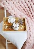 Tazza con cioccolata calda, ciotola con le caramelle gommosa e molle, barattolo con cioccolato, plaid gigante pastello rosa immagini stock
