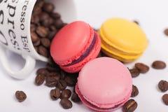 Tazza con i chicchi di caffè con i maccheroni francesi deliziosi variopinti sulla fine bianca del fondo su Immagini Stock