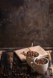 Tazza con i chicchi di caffè a fondo di legno scuro Immagini Stock Libere da Diritti