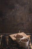 Tazza con i chicchi di caffè a fondo di legno scuro Immagini Stock