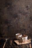Tazza con i chicchi di caffè a fondo di legno scuro Fotografia Stock Libera da Diritti