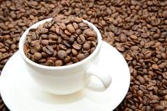 Tazza con i chicchi di caffè su un piattino Immagini Stock