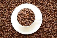 Tazza con i chicchi di caffè su un piattino, vista dalla cima fotografia stock