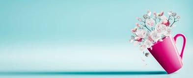 Tazza con il mazzo grazioso del fiore della molla di magnolia e di petali di caduta a fondo blu-chiaro, fine su Disposizione di f fotografia stock libera da diritti