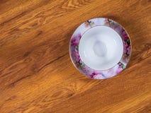 Tazza con il piattino sulla tavola Fotografia Stock Libera da Diritti
