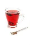 Tazza con il tè floreale ed il cucchiaino da tè del carcade rosso caldo Fotografia Stock