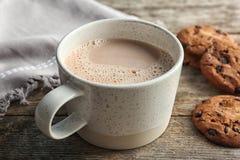 Tazza con la bevanda ed i biscotti caldi deliziosi del cacao immagine stock