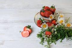 Tazza con le fragole ed i fiori selvaggi Fotografie Stock Libere da Diritti