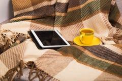 Tazza con tè e la compressa su un plaid di lana a quadretti Immagine Stock