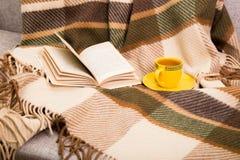 Tazza con tè ed il libro aperto su un plaid di lana a quadretti Immagine Stock