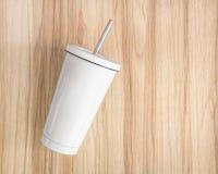 Tazza d'acciaio bianca con il tubo su fondo di legno Il contenitore isolato per tiene la vostra bevanda immagini stock